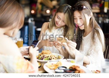 happy friends with smart phones taking picture of food at restaurant