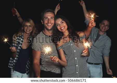 Happy friends with sparklers on beach party