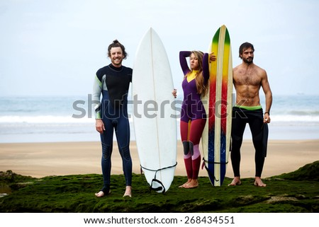Happy friends with surfboards on tropical beach, summer lifestyle concept, group of friends having fun on seashore  - stock photo