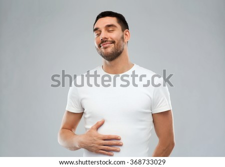 happy full man touching tummy over gray background