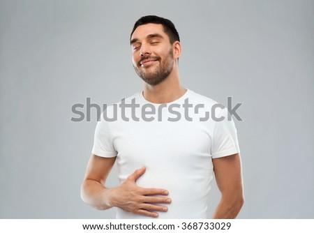 happy full man touching tummy over gray background - stock photo