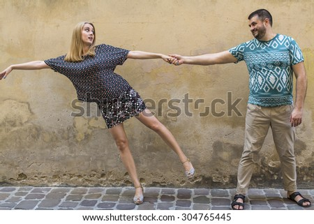 Happy fun couple in love on the street in front of a stone wall. - stock photo