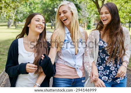 happy fun teen girl friends walking in park laughing on weekend - stock photo