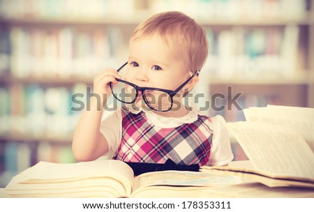 Happy funny baby girl in glasses reading a book in a library - stock photo