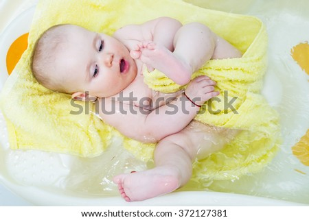 happy funny baby laughing and bathed in the bath with yellow towel - stock photo