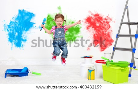 happy funny child girl doing repairs, jumping and paint the wall at home - stock photo