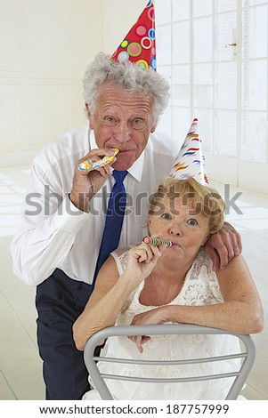 Happy funny elderly couple in festivity blowing and making noise - stock photo
