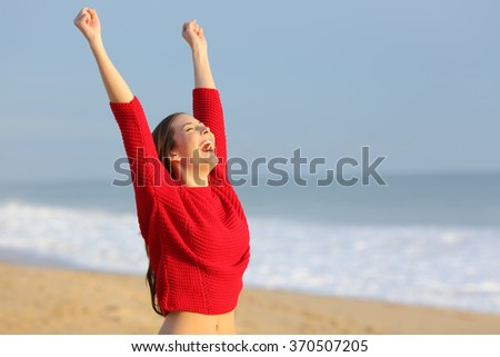 Happy funny excited woman wearing red color sweater raising arms euphoric on the beach at sunset with a warm light in the background - stock photo
