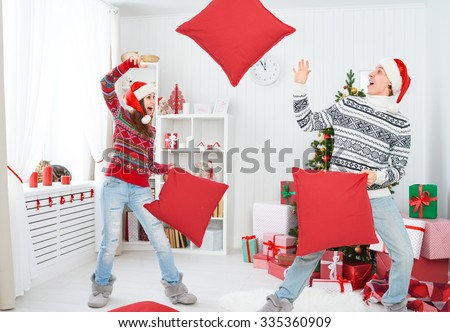 happy funny family loving couple laughing and fighting on pillows on Christmas morning  - stock photo