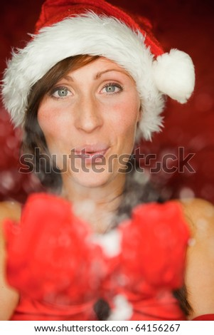Happy funny female portrait blowing snowflakes
