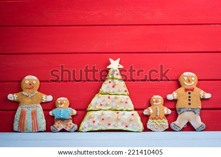 Happy funny gingerbread man family on wooden background with Christmas tree - stock photo