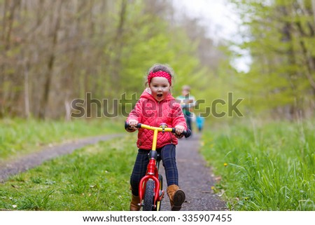 Happy funny kid girl and colorful raincoat riding his first bike on summer day. Active leisure for children outdoors. - stock photo