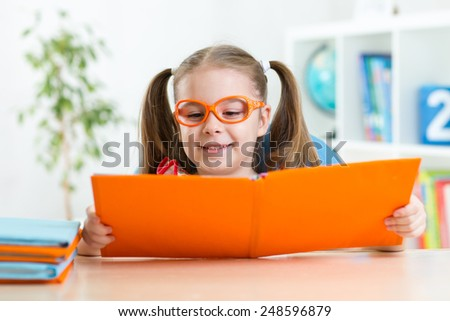 Happy funny kid girl in glasses reading a book in primary school