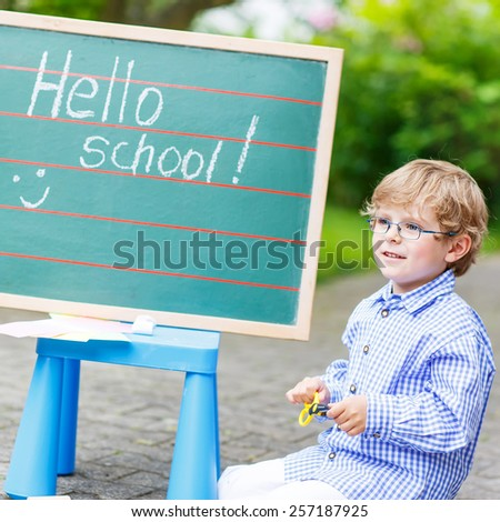 Happy funny little child with glasses at blackboard practicing writing, outdoor. school or nursery. Back to school concept - stock photo