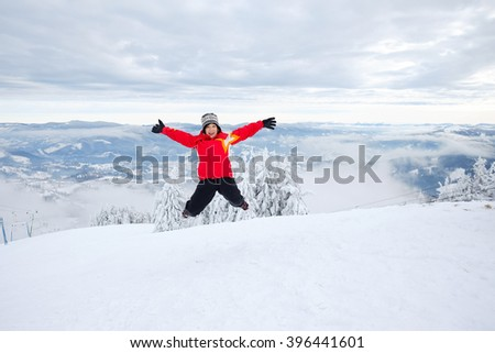 Happy, funny, little girl, child, kid jumping on the mountain hillside, having fun outdoors on mountain skyline in front of beautiful pine trees in winter. Travel background with mountains and snow.