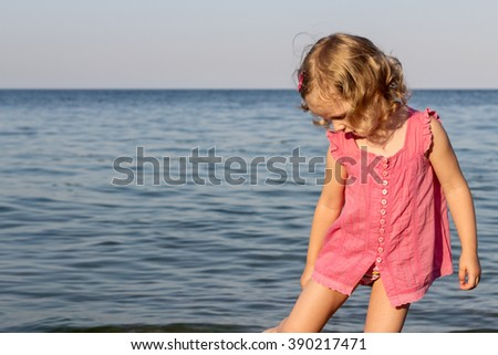 Happy, funny little girl on the sea. Selective focus.