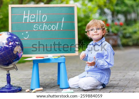 Happy funny little kid boy with glasses at blackboard practicing writing, outdoor. school or nursery. Back to school concept - stock photo