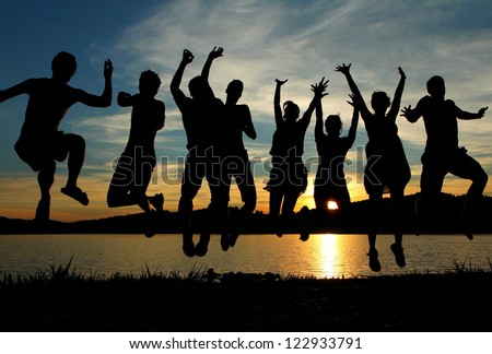 Happy funny people jumping in the sunset on the beach - stock photo
