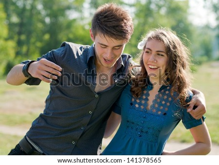 Happy funny teenage couple dancing outdoors and laughing on the bright sunny day & green summer background - stock photo