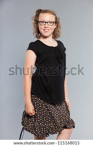 Happy funny teenage girl with curly blonde hair. Wearing glasses. Expressive face. Studio shot isolated on grey background. - stock photo