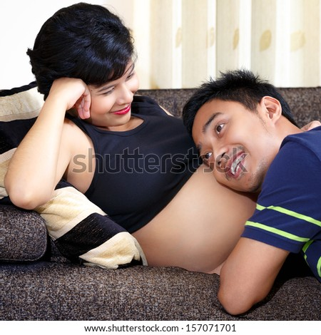 Happy future dad listening the belly of his pregnant wife - stock photo