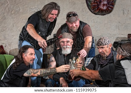 Happy gang members toasting with bottle of liquor