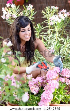 Happy gardener pruning flowers and plants. Caucasian beautiful brunette woman smiling outdoor. - stock photo