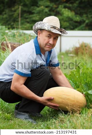 Happy gardener with melon in hands - stock photo