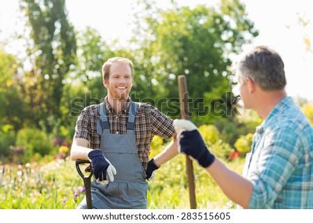 Happy gardeners talking at plant nursery - stock photo