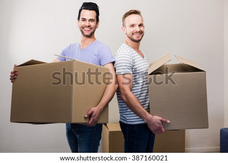 Happy gay couple holding boxes at new home - stock photo