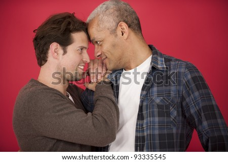 Happy gay couple in love on red background - stock photo