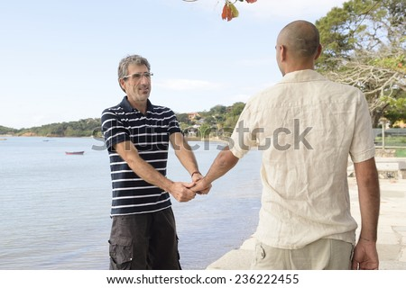 Happy gay couple on vacation holding hands - stock photo