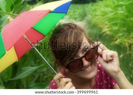 Happy gay girl with a multi-colored umbrella. - stock photo