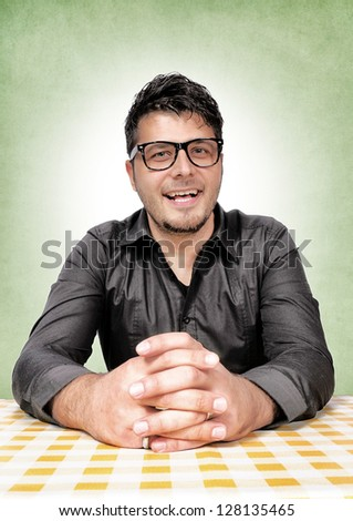 Happy geek siting on the table - stock photo