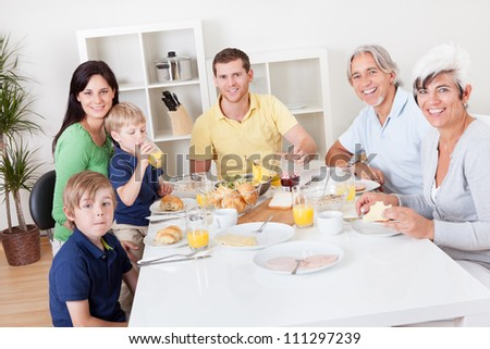 Happy generations family having breakfast together in the house - stock photo