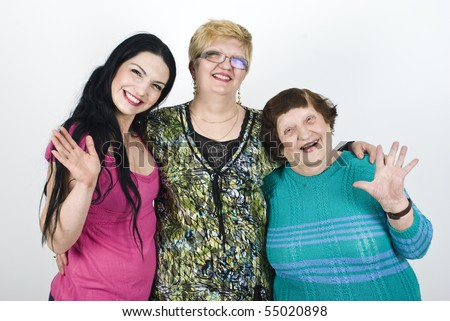 Happy generations of women grandmother,mother,daughter standing in a embrace  waving and laughing