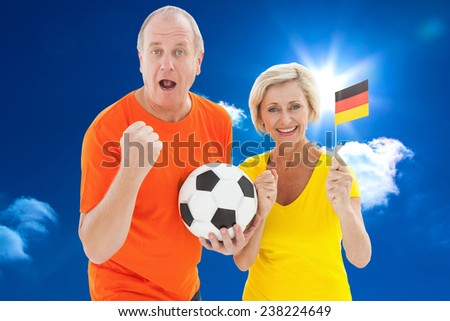 Happy german couple cheering at camera holding ball against bright blue sky with clouds - stock photo