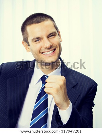 happy gesturing businessman at office, success in business concept - stock photo