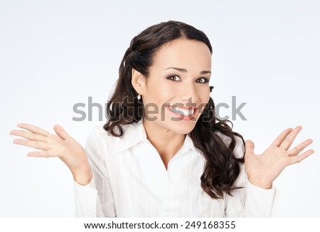 Happy gesturing smiling business woman, against grey background - stock photo