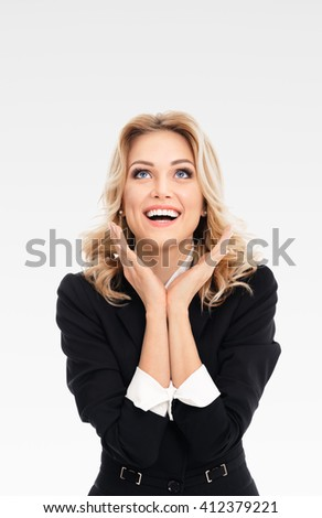 Happy gesturing young cheerful businesswoman, on grey background, with blank copyspace area for text or slogan - stock photo