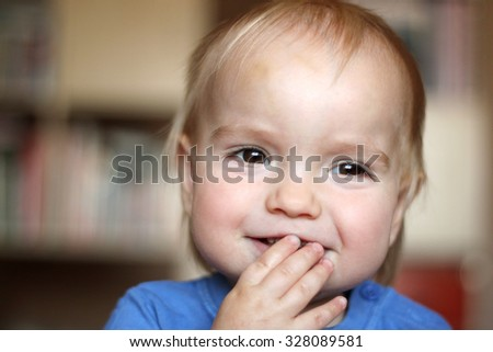 Happy giggling toddler boy putting his hand to the mouth, indoor portrait - stock photo