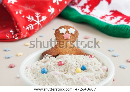 Happy gingerbread man taking a bath in a cup with wholegrain flour and Christmas decoration.