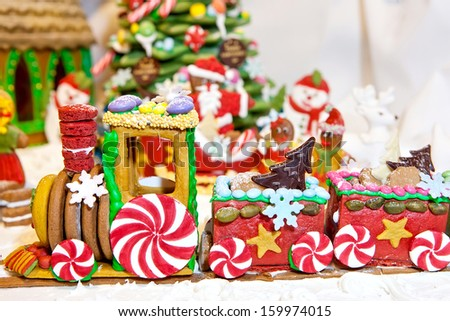 Happy gingerbread people gathered by the christmas tree looking at train as Christmas fun decoration