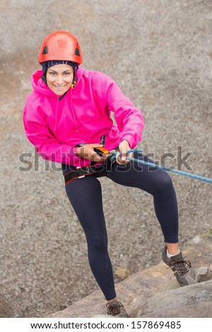 Happy girl abseiling down rock face looking up at camera - stock photo