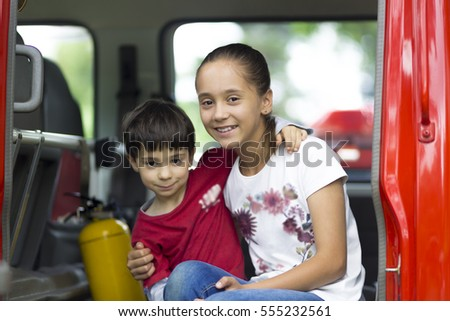 Happy Girl and Boy in Firefighter Car Enjoying Outdoors