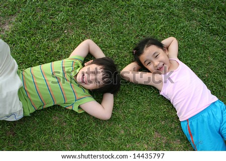 Happy girl and boy lying on the grass - stock photo