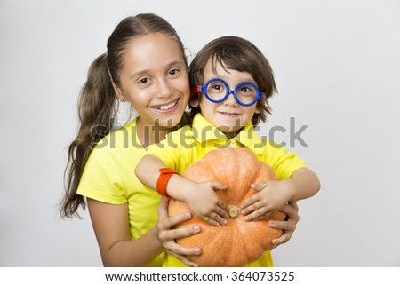 Happy Girl and Boy Playing with Pumpkin, Eating Healthy Food - stock photo