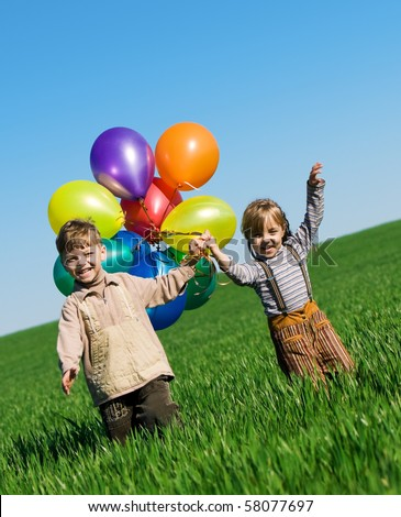 Happy girl and boy with balloons walking on the spring field