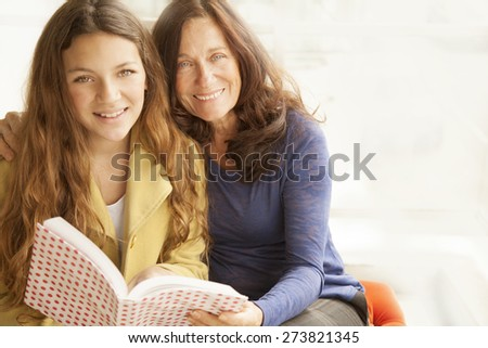 Happy girl and grandmother studying with book - stock photo