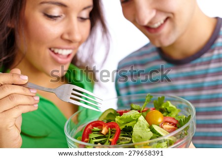 Happy girl and her boyfriend eating fresh vegetable salad - stock photo
